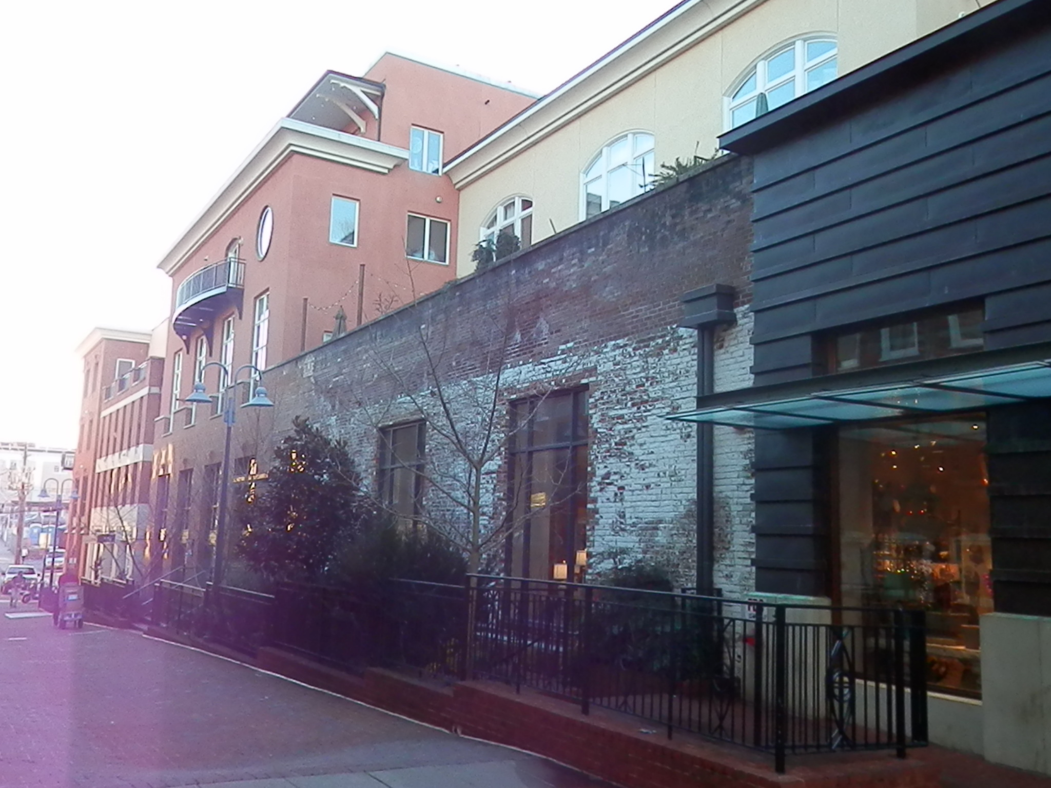 (the side of the building has multiple facades, including metal, faded brick, normal brick, and stucco)
