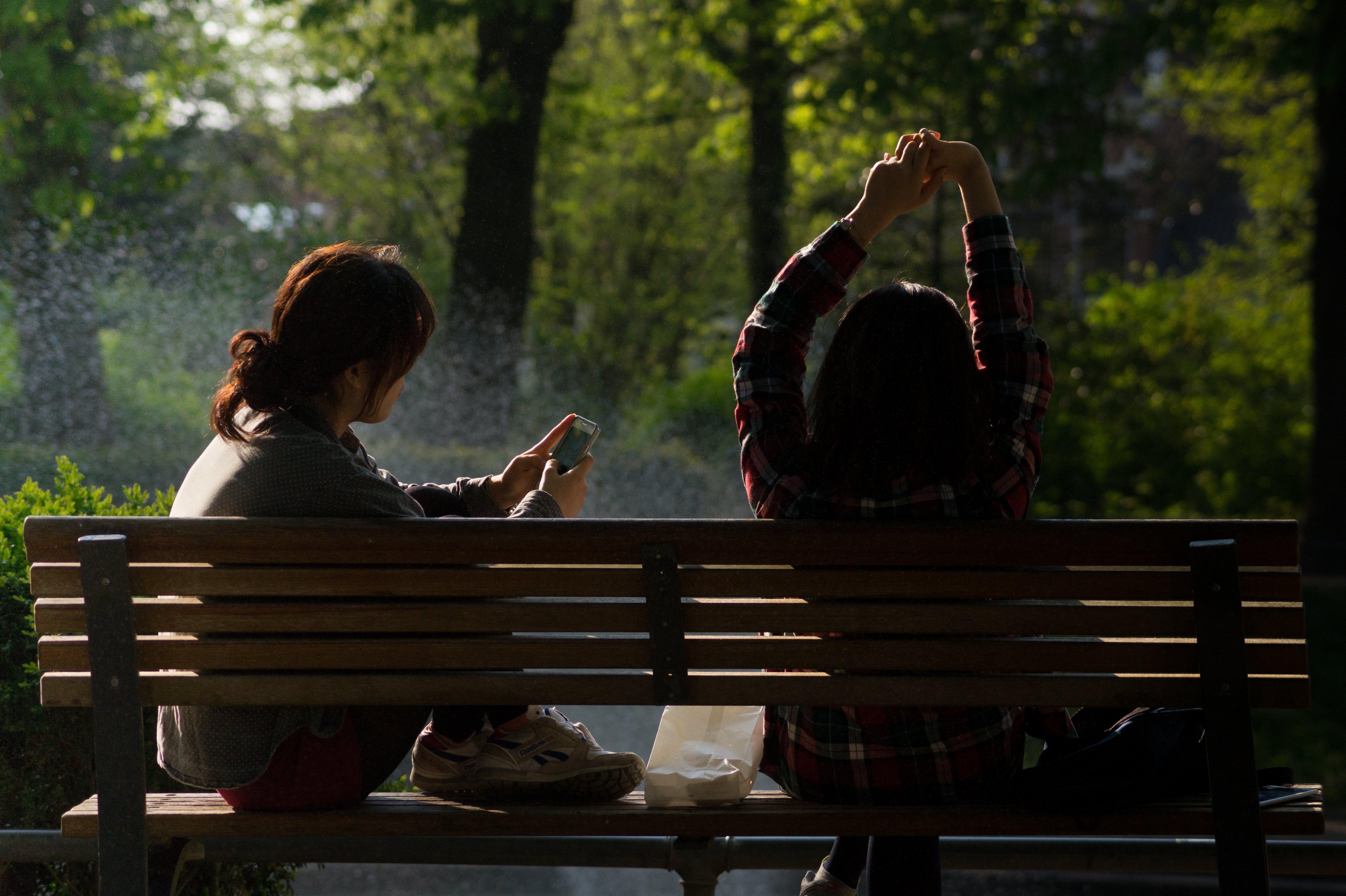 Woman sitting on a bench in a park using a smartphone