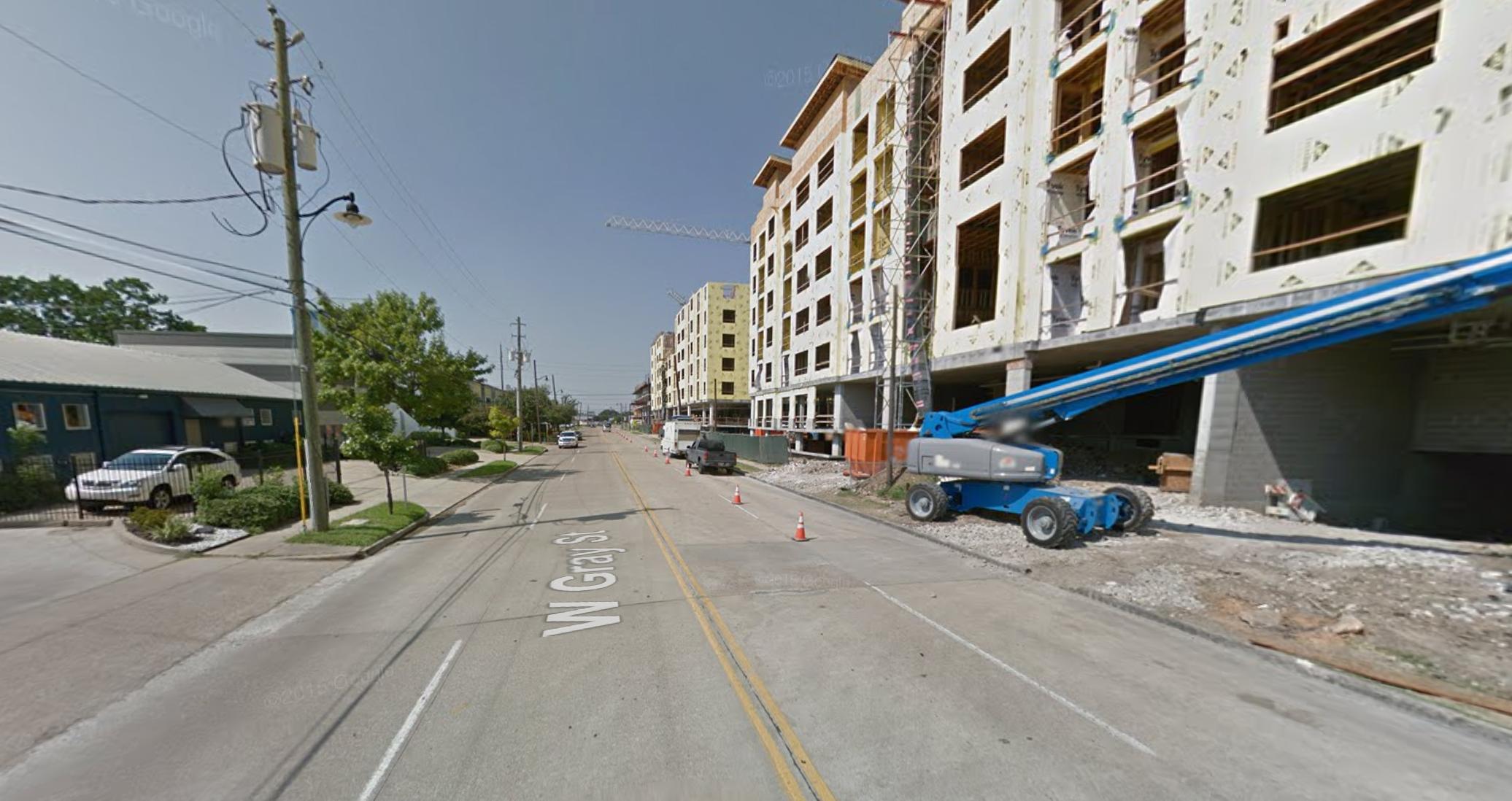 A four-lane road cutting through an urban neighborhood.